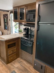 Kitchen features a refrigerator/freezer, a small gas stovetop, small oven, large sink, microwave and Keurig coffee machine